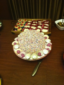 Rainbow Sprinkle Caje surrounded by Cookie Dough Truffles